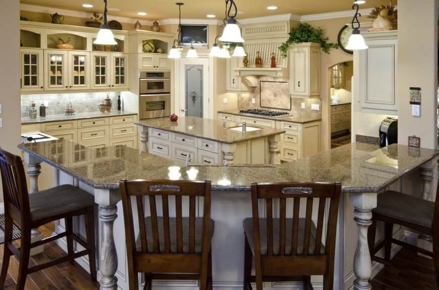 This homely kitchen has a large geometric island with a broad marble top and a smaller one with drawers and cabinets to accommodate storage. Lit brightly by daffodil lamps overhead, the kitchen has a cool theme of stone and cream, giving it a homely feel.