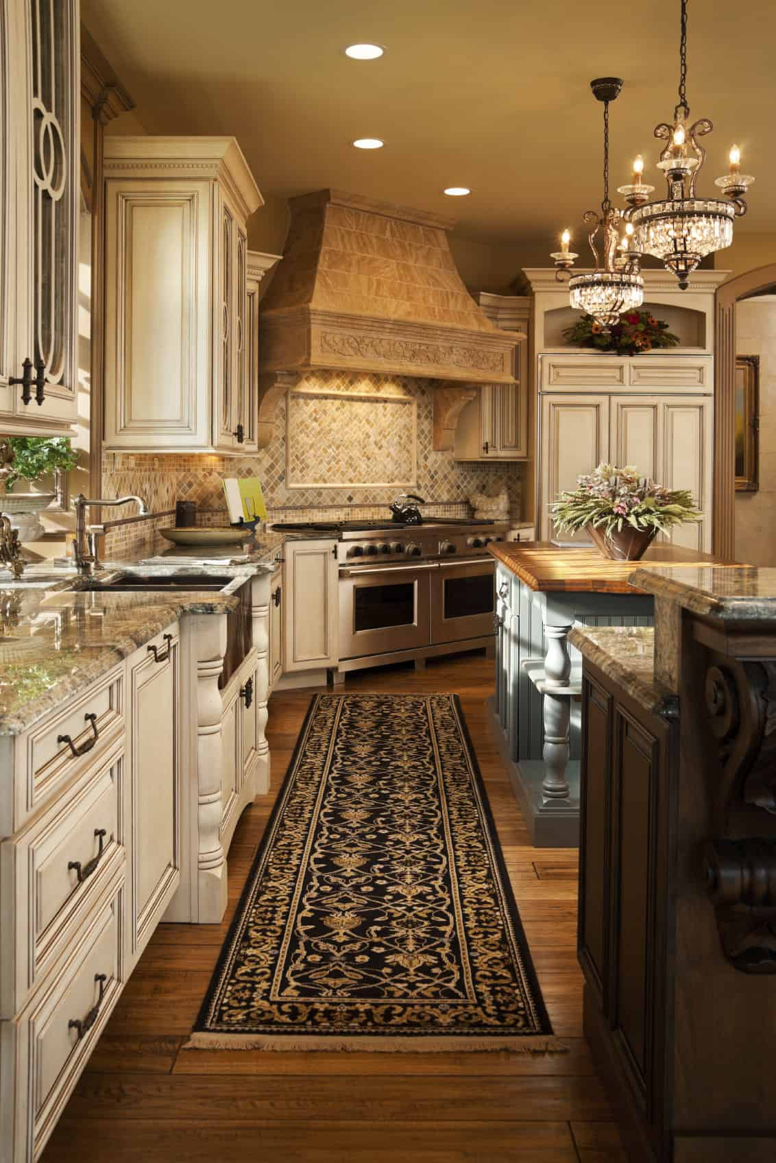 This happy kitchen has large but compact islands with carved wood bottoms. Above are gorgeous hanging chandeliers and lights fitted into the ceiling, and alongside the kitchen wall are the appliances and storage drawers.