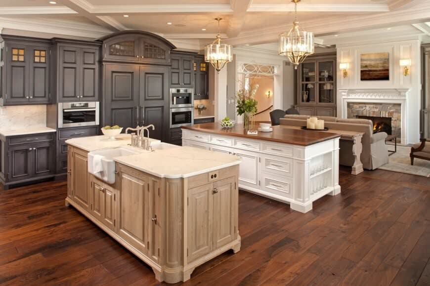 This cheerful kitchen incorporates a cozy living room and hearth behind the large islands with marble and wooden tops. Ceiling lighting adds soft light, and appliances and storage cupboards are aligned to the wall with dark wood, complimenting the floor.
