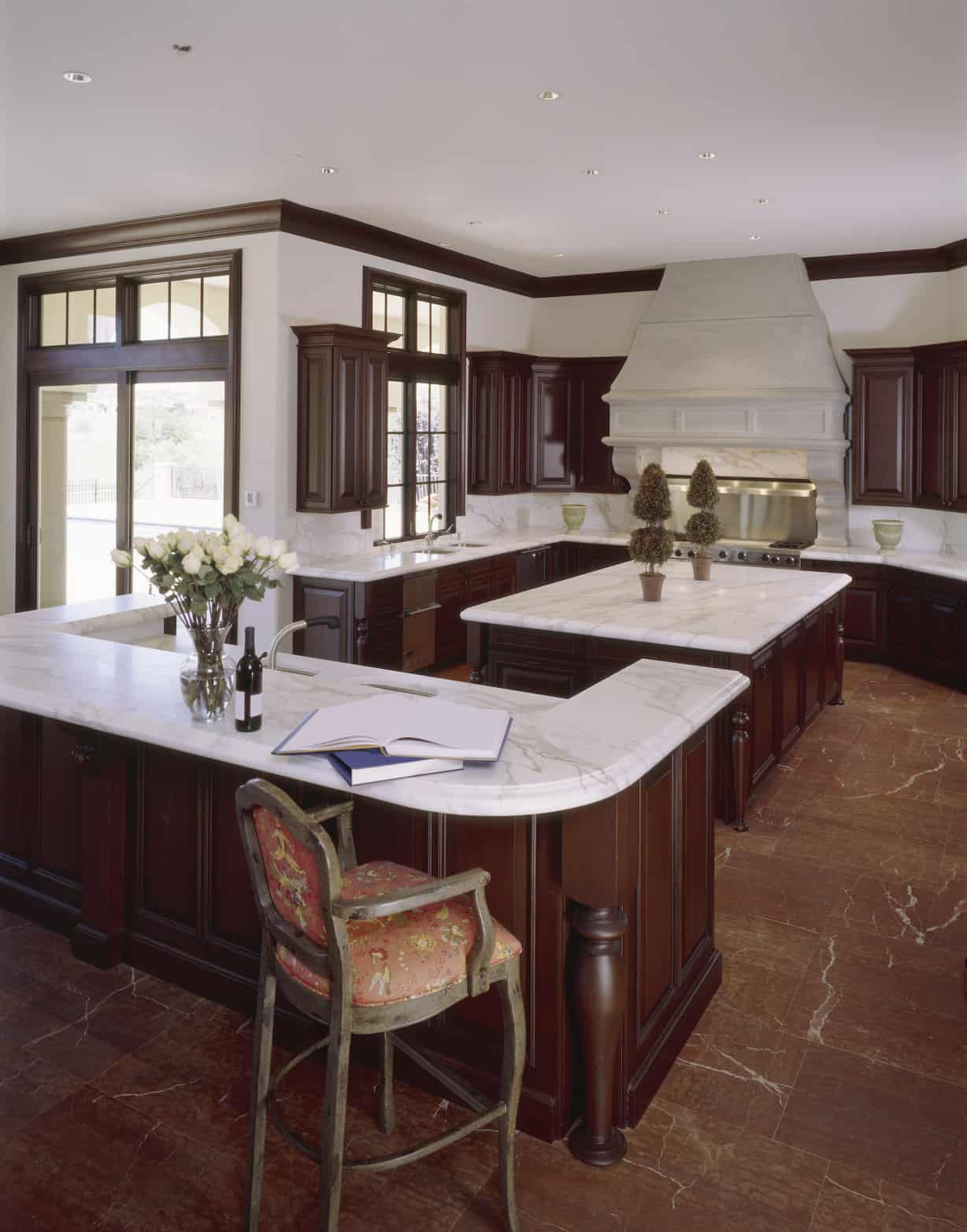 The monotone kitchen used wood, marble and geometry to boast of its islands and architecture. With smooth countertops making kitchen work easy to do and with lot of natural light and soft indoor lighting, this kitchen is perfect to dine in.