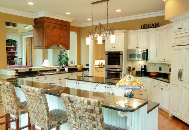 This cheerful kitchen boasts themed marble with a well lit ceiling. It has a cascading island to serve as a bar and dining besides a more voluminous one for meal prep. Located centrally, this kitchen is the hearth of a home.
