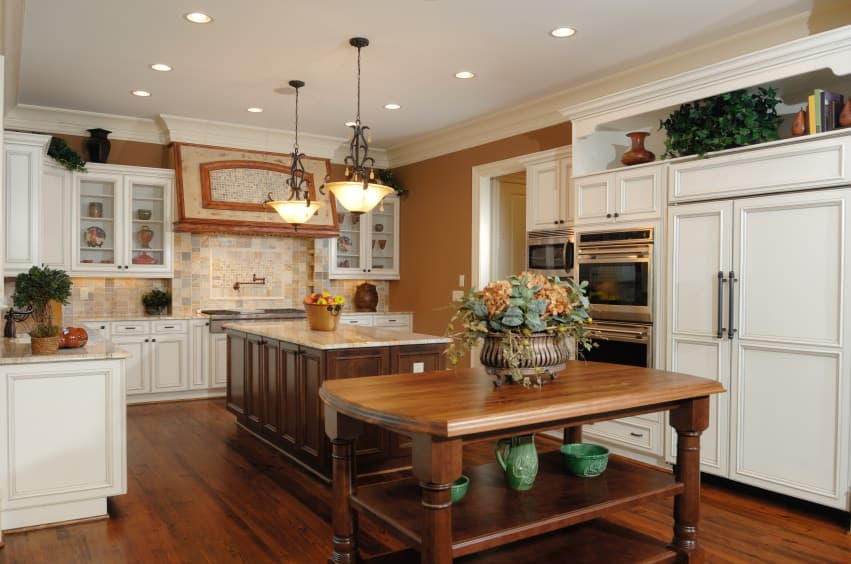 With appliances, refrigerators and ovens relegated to the corners, the kitchen makes way to star its large marble and wood islands. Under embellished bowl lamps, the egg shell island is a perfect place to dine on and cabinets on the side are perfect for storage.