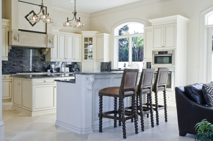 This chill kitchen has soothing white tones contrasted by the dark marble tops of the islands reflecting the elegant chandeliers overhead. With lots of sunlight and comfortable highchairs, it's an elegant yet cozy place.