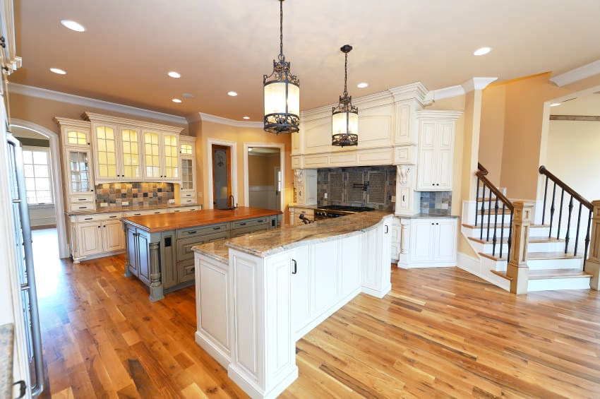This roomy kitchen is centrally located with two counters with cabinets and drawers, ready for storage and ready for dining use. The woodwork and lamps create a lovely warm ambiance to this construction.