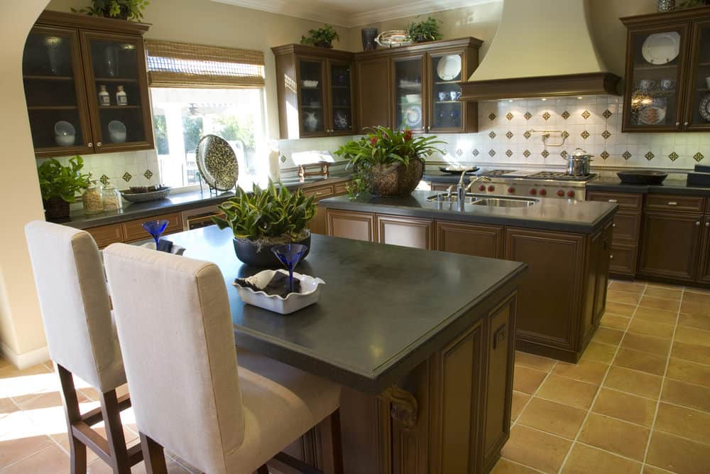 For those who love earthy hues, this compact kitchen is perfect for a small family. The side counter tops accommodate comfy chairs. The natural lighting and low indoor lighting go perfectly with the flooring.