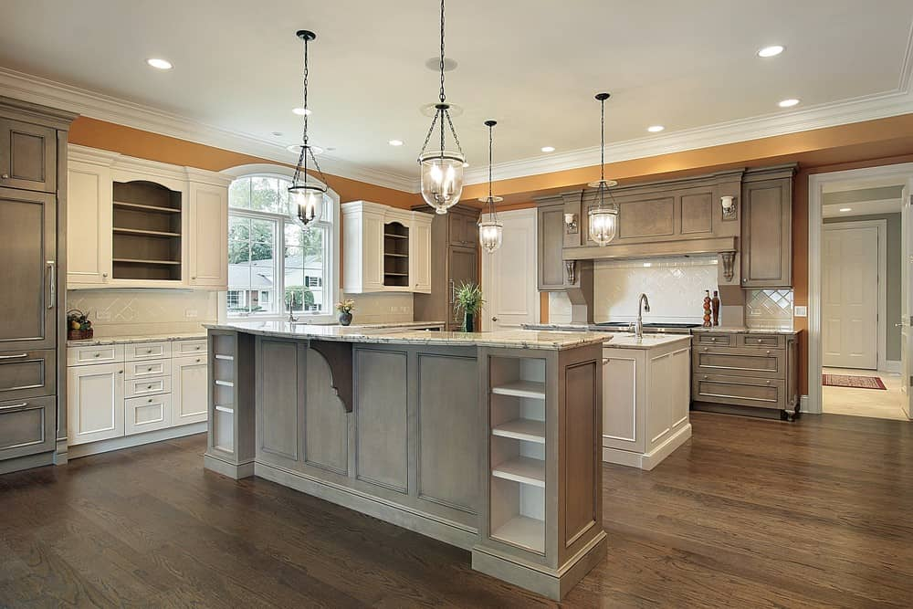 This elegant and spacious kitchen has two large islands, under modern lamps, with small shelf space on their sides. Behind the islands is the stove and on their sides are the appliances and cabinets fixed into the walls, and in the middle is a lovely window adding the right amount of natural light.