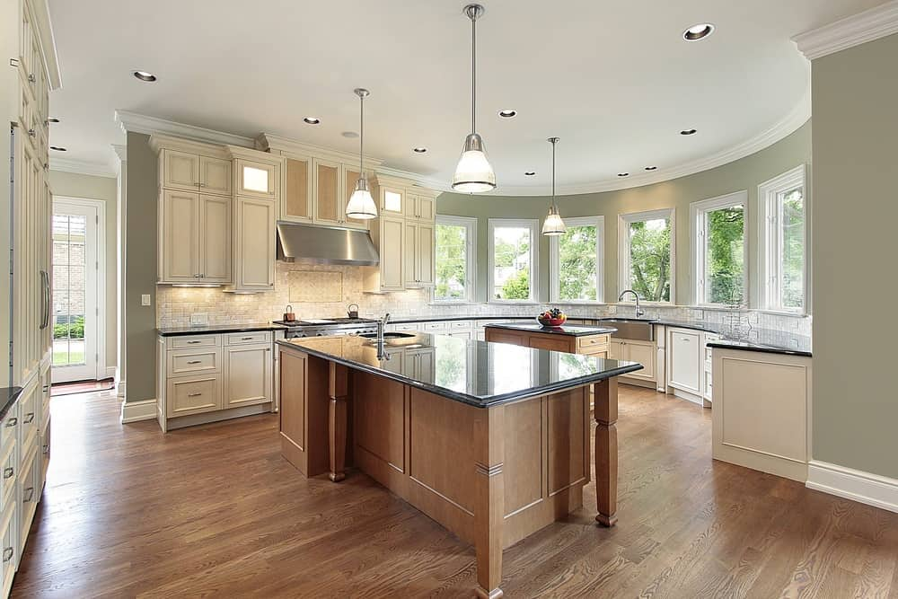 This geometrically architectured kitchen stars a large island with a sink and a smaller one under spread out overhead lamps. With lots of natural light and subtle appliance fixtures, this kitchen is one of the neatest designs.