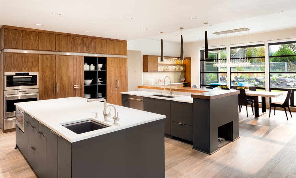 The large monotone islands are the star of this well lit kitchen. The hanging lamps and wide window add perfect lighting to the kitchen. Appliances and cupboards are fixed into the walls, making the room look bigger.