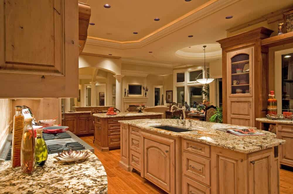 This large kitchen has multiple islands with smooth countertops. The walls are lined with cabinets for storage and the marble work compliments the soft woody color theme. Soft lighting accentuates the architecture of this spacious kitchen, perfect for a big family.
