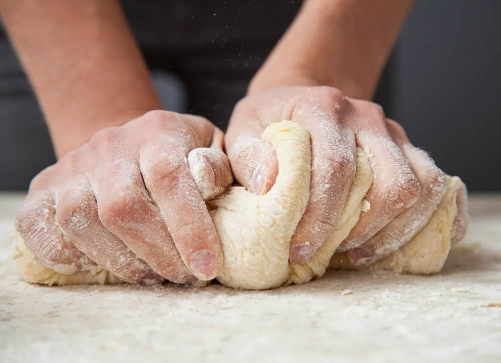 Kneading dough by the hand.