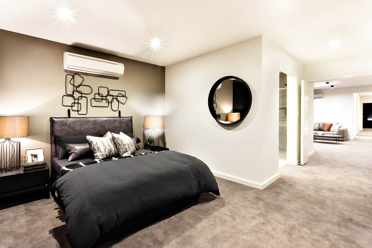 Black is always an option. This primary bedroom is all about the contemporary interiors. You've got the metallic wall hangings on the wall that look like an abstract sculpture. Then there is the beautiful round ebony mirror and a pair of charcoal black nightstands. You can never go wrong with black and white combination.