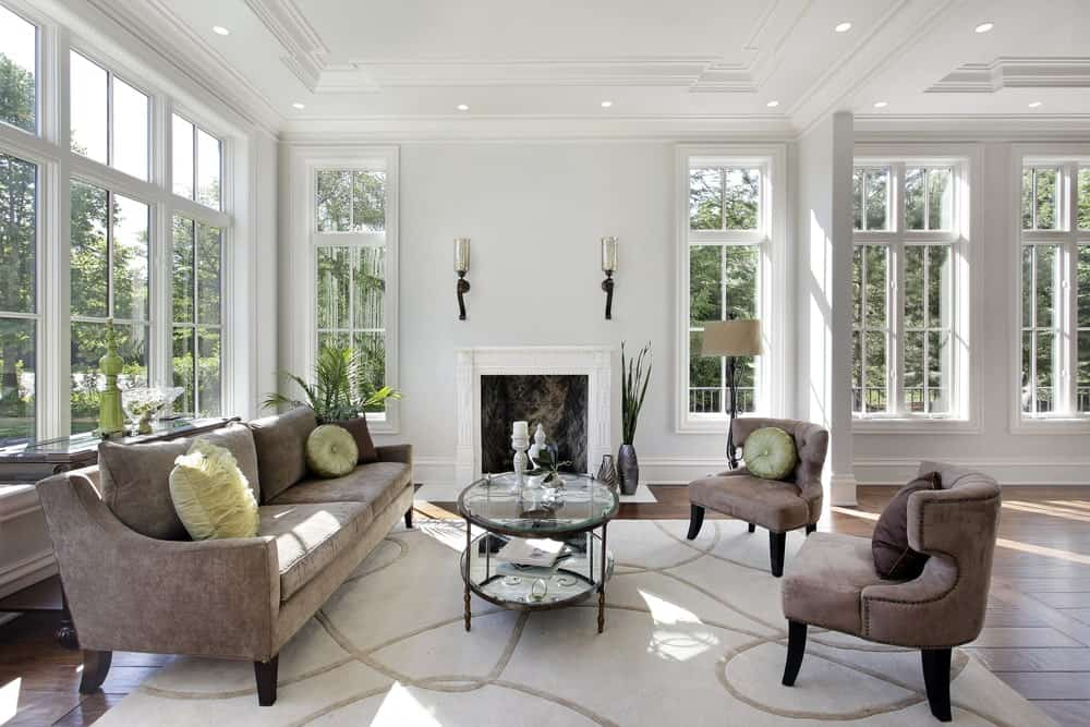 Luxurious white living room with large windows.