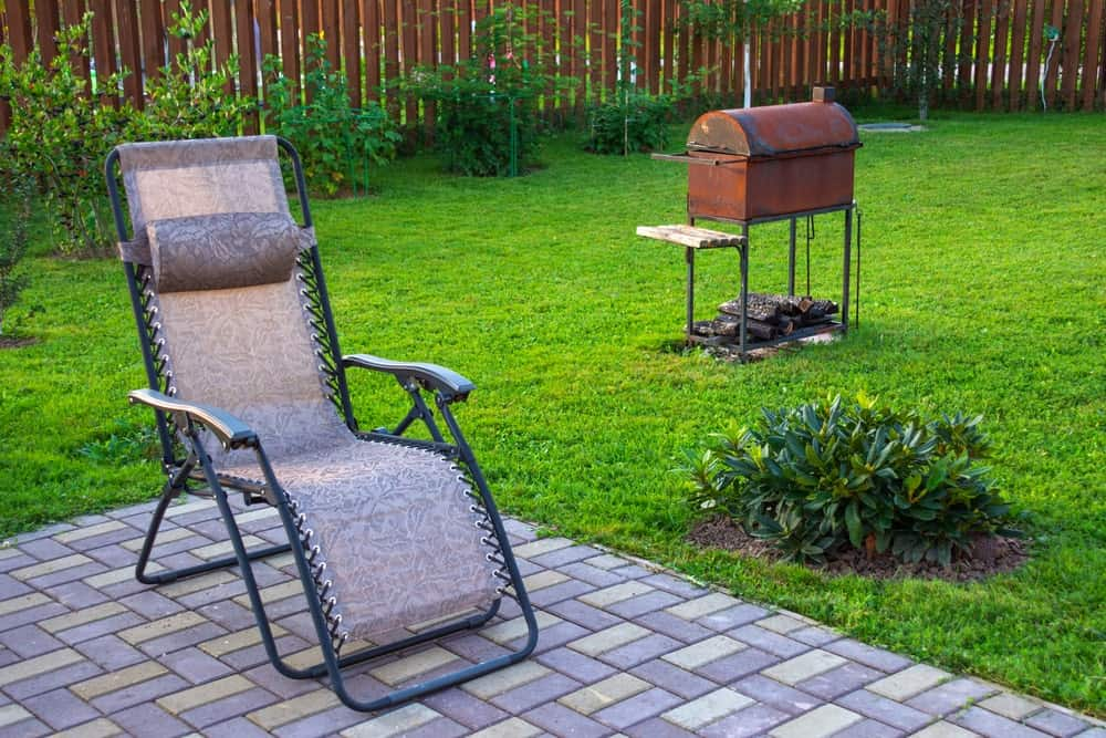 A patio lounge chair on a paved flooring near the lawn with an outdoor grill.
