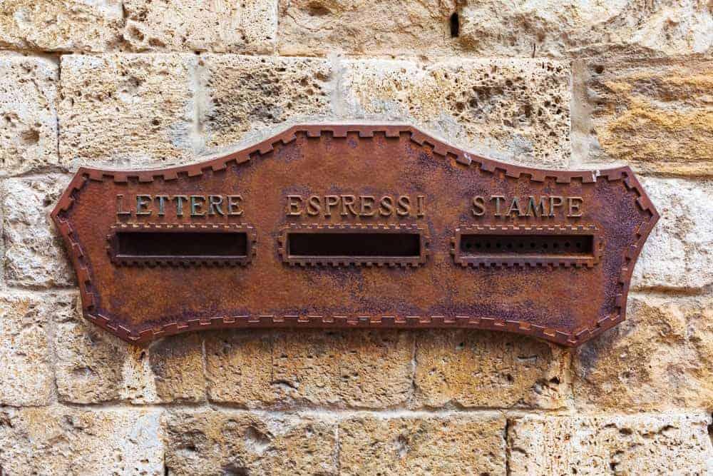 Vintage mail slot on stone brick wall.