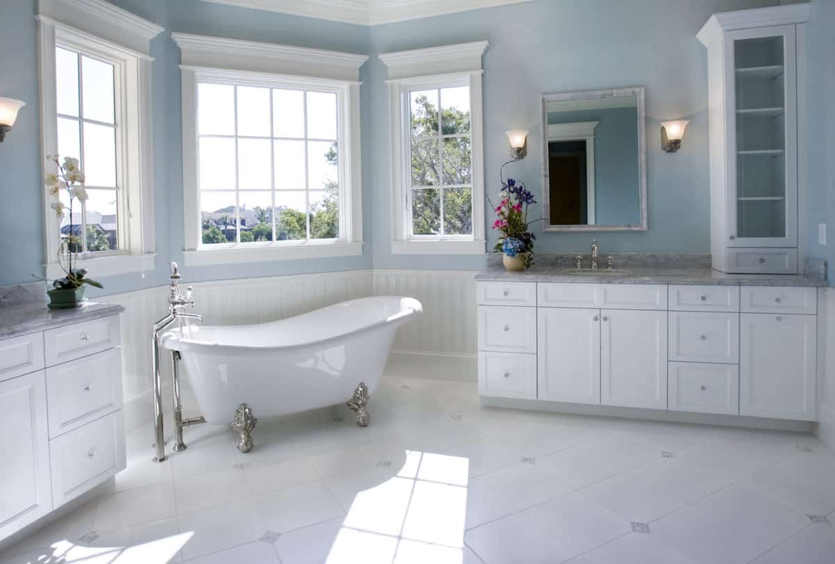 This bathroom is super-feminine with its pale aquamarine walls and the many fripperies on top of the towel closet. The soft shades are enhanced by the natural lighting coming from the open windows above the bath tub.