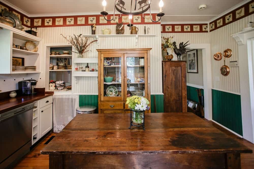 Farmhouse kitchen with open shelving and wooden furniture.