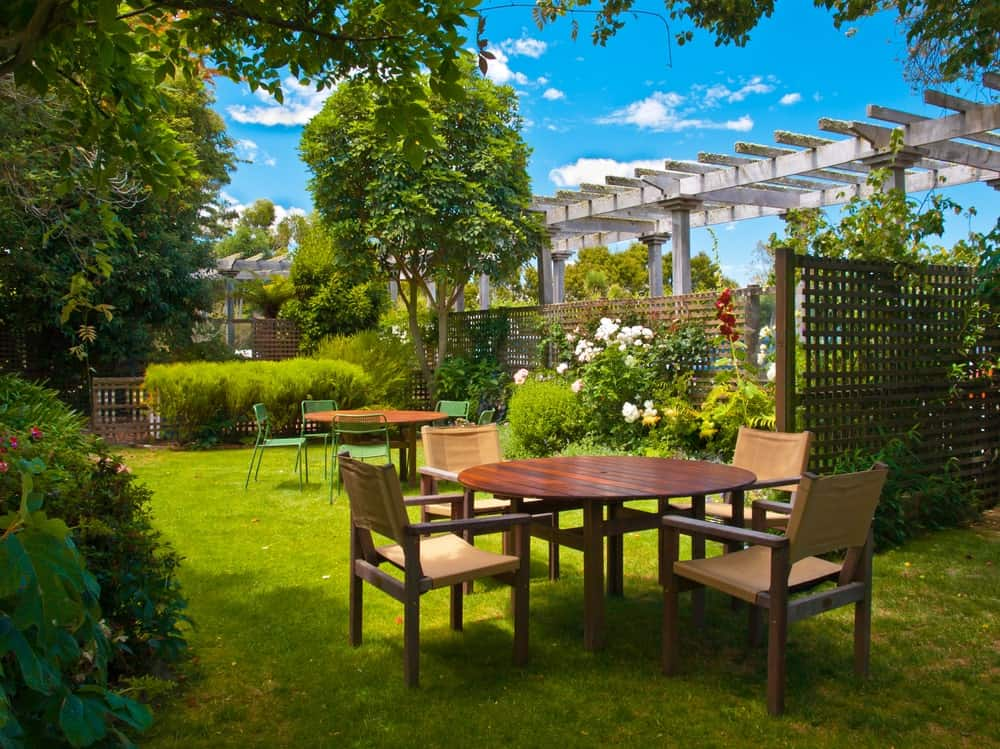 Garden patio with pergola and outdoor dining sets under the shade of trees.