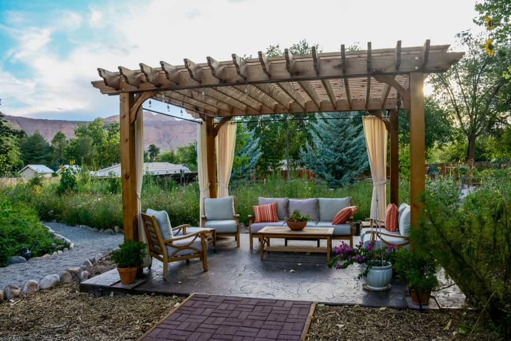 An outdoor living space in the garden under a pergola.
