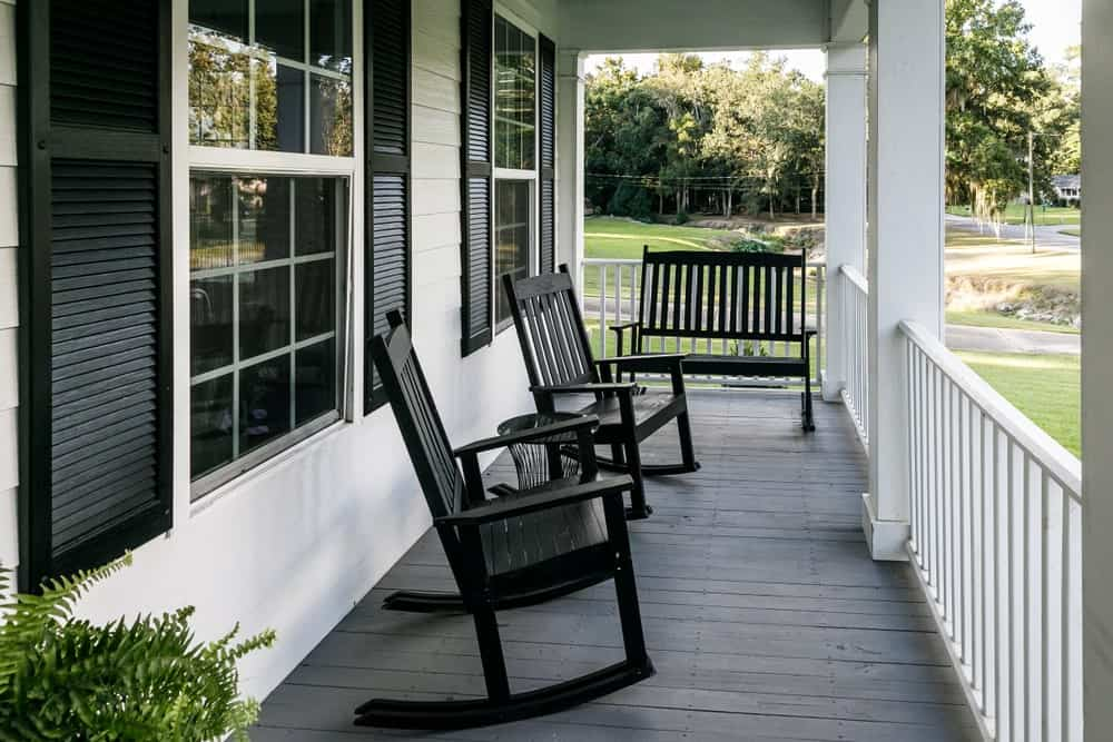 Porch of a Southern home with black window shutters and rocking chairs.