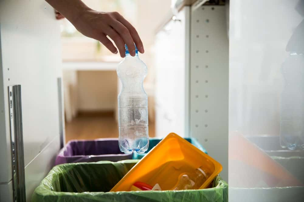 Placing the empty plastic bottle on the recycling bin in the kitchen.
