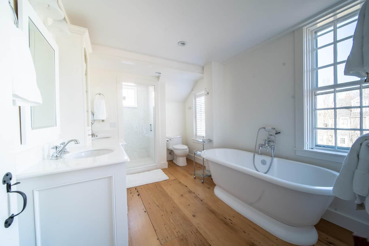 The wide-plank hardwood flooring and window tell you that this spacious white master bathroom is part of an older home.  This is a colonial house built in 1735 but has since been beautifully remodeled.