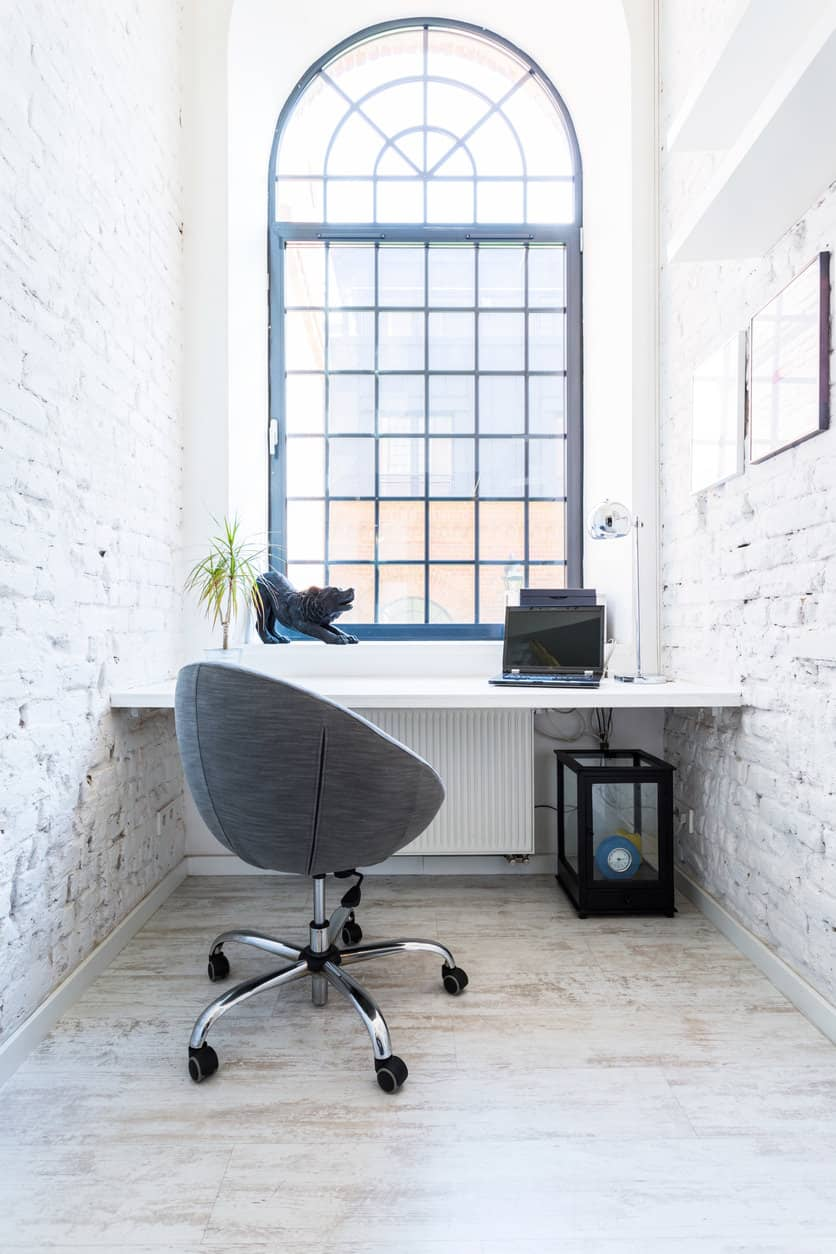 Here's a tiny room with a full-width desk, large arched window with original brick walls painted white. While small, this is a comfortable and attractive place to work. This is a fabulous example of a small home office.