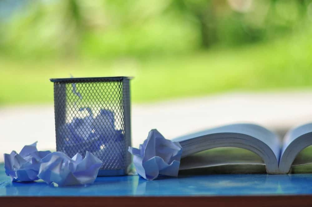 Small wastebasket for crumpled white papers beside an open book.