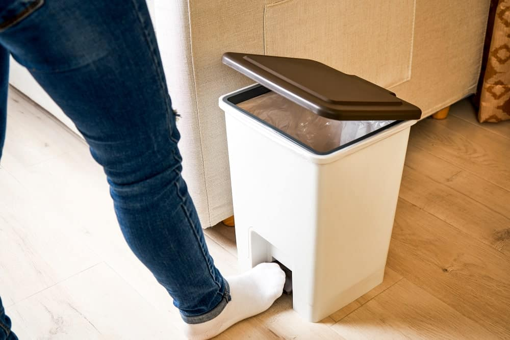 Opening the step wastebasket by stepping on the lever.