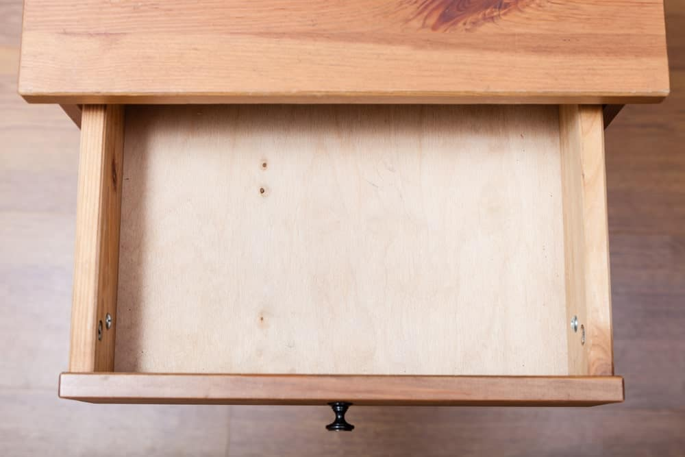 Top view of an open wooden storage drawer.