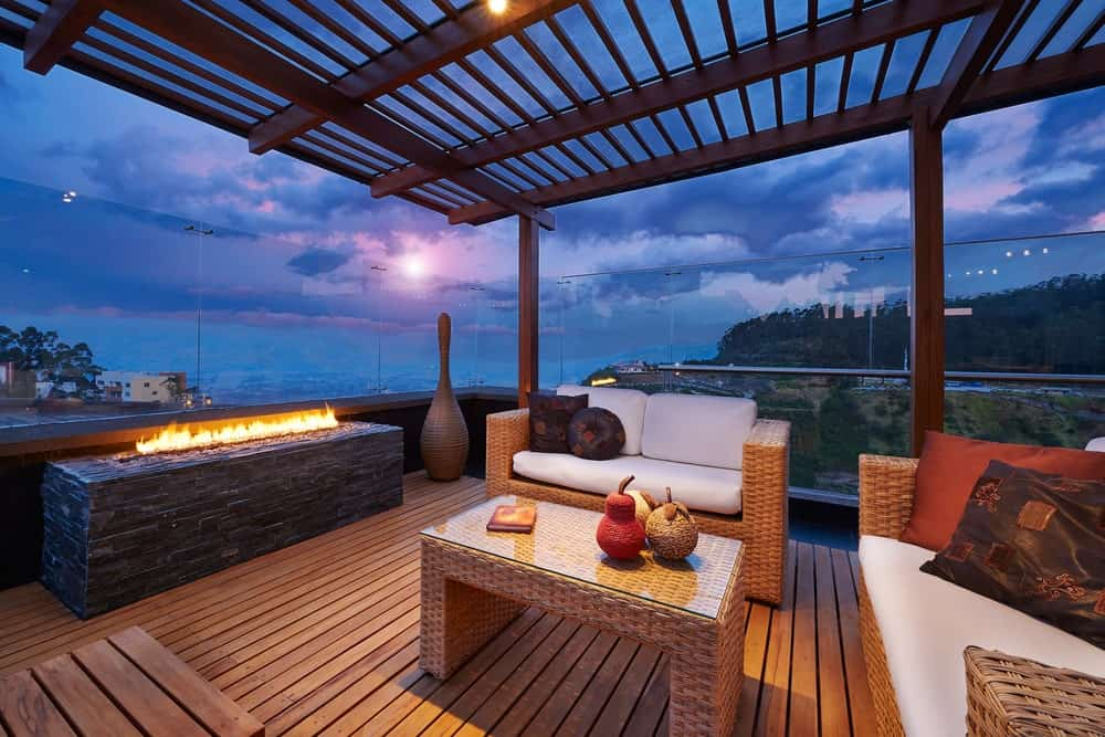 Decked terrace under a pergola with glass railing, fire pit, and outdoor furniture during sunset.