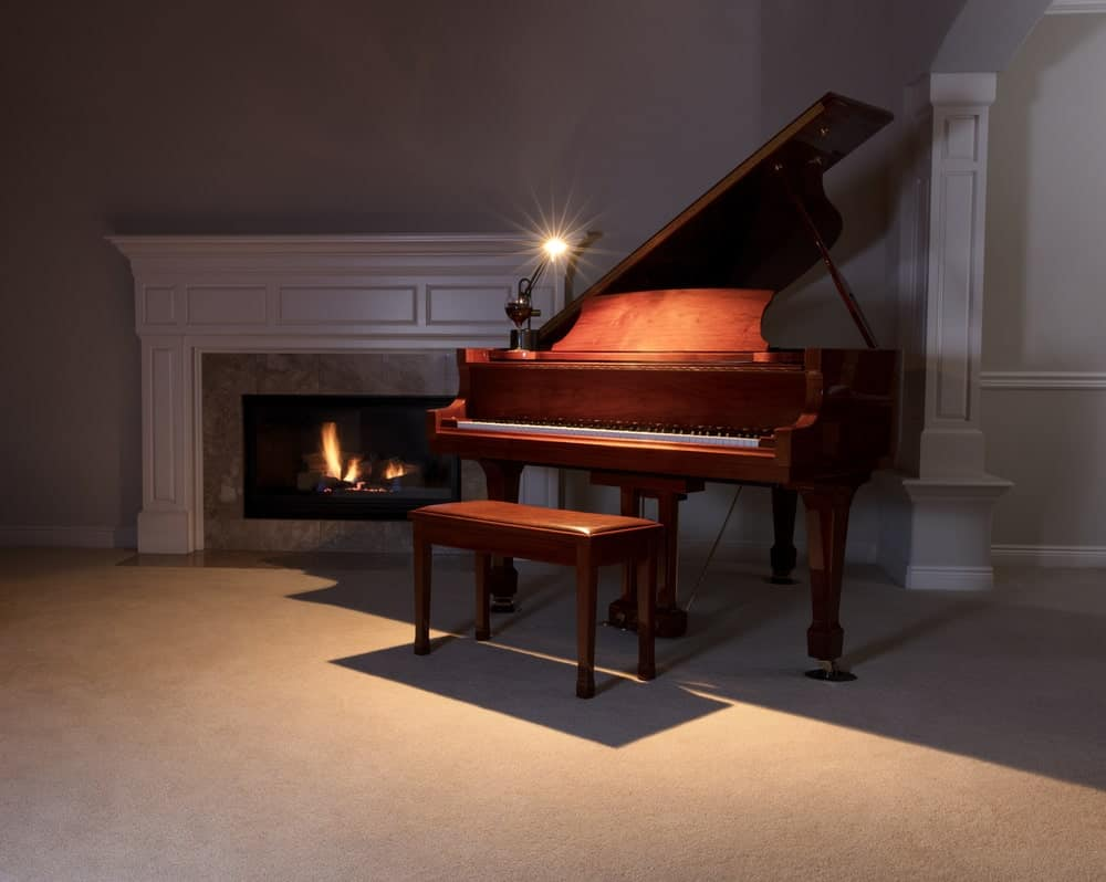 Traditional fireplace beside a wooden grand piano.