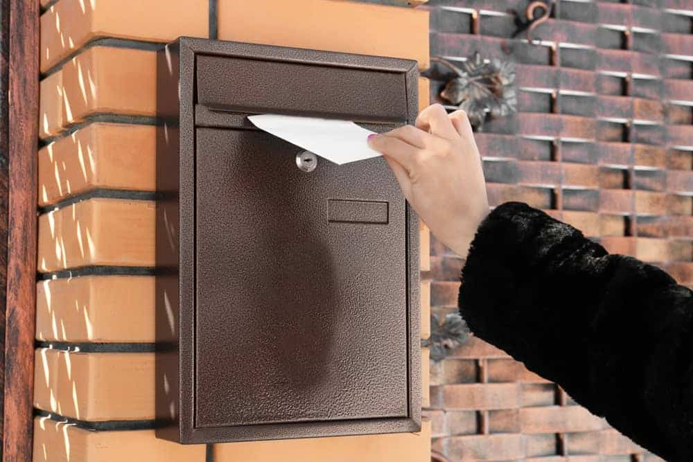 Hand inserting a mail inside a wall mount mailbox.