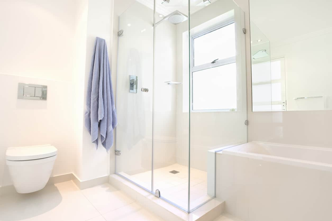 The modesty of the pure white walls and standard sized off white tiles compliment the modern elements of the wall mounted inverted pyramid shaped toilet basin. The glass panel enclosed walk in shower and perfectly rectangular bathtub to make modern elements combine with modest touches to create this clean feeling fresh bathroom.
