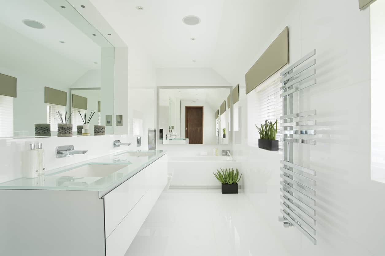 Modern sleek styling combine with chrome glimmer and polished gloss to make for a brilliant result when the sun shines through the large window. The ultra large oversized mirror covers most of the vanity wall of this spacious master bath. A large garden tub with chrome fixtures fits together with the square shaped toilet basin and translucent glass counter top and inset square sink basins to maximize the modern look.