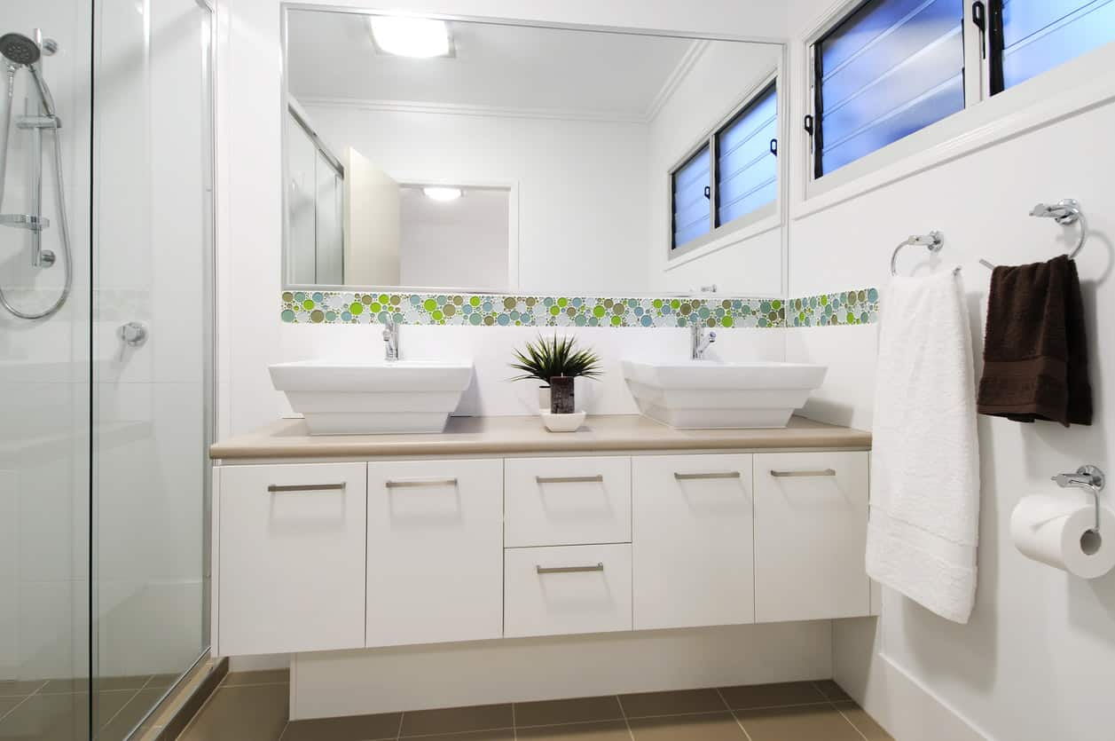 A large walk in glass panel enclosed shower combines with a strip of mosaic style green and blue tile that horizontally follows the walls, and two inverted pyramid shaped sink basins match the contemporary solid panel style cabinet vanity. Quaint but modern, this bathroom combines comfort and simplicity in an efficient way.