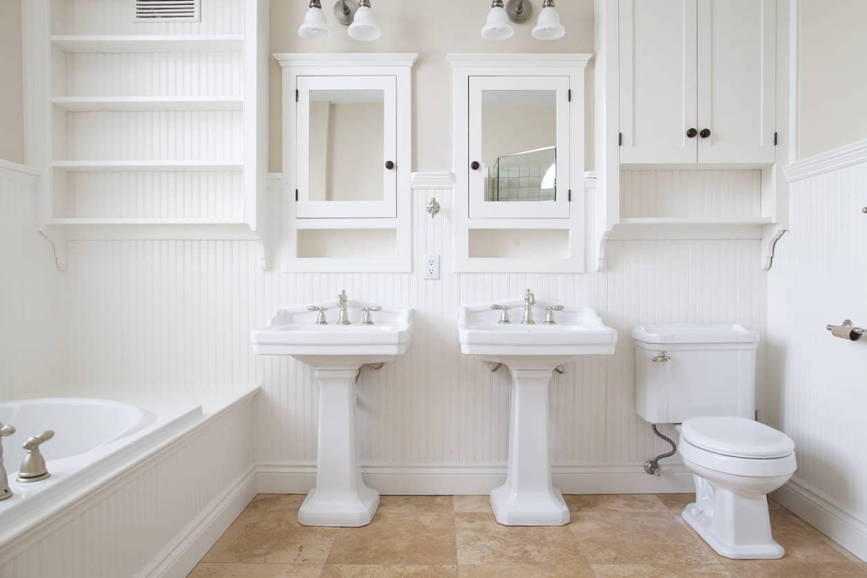 Centered around two southern manor styled freestanding sinks and wall mounted mirror door cabinets, this bathroom looks like it comes right out of the home and gardens magazine. Elaborate white crown molding and white carved baseboards come together with the white wood paneling lining the walls to tie it all together.