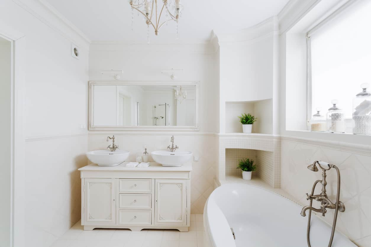 Built around a large wall spanned window, this white tiled master bath with a pure white vintage style vanity with twin bowl sinks and brushed vintage look copper colored fixtures feels like a sensation of elegance. White crown molding and a large oval partially free standing garden bathtub make for a relaxing bathing experience.