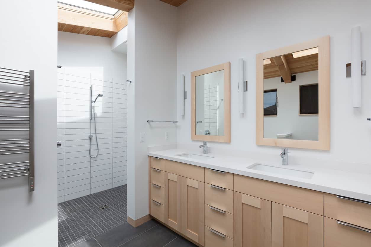 Light pine colored cabinets and skylight window frame with a sharp modern style combine with the bright white walls and counter tops of this Master bath to create a contemporary relaxing shower experience right under the moonlight in the spacious walk in shower.