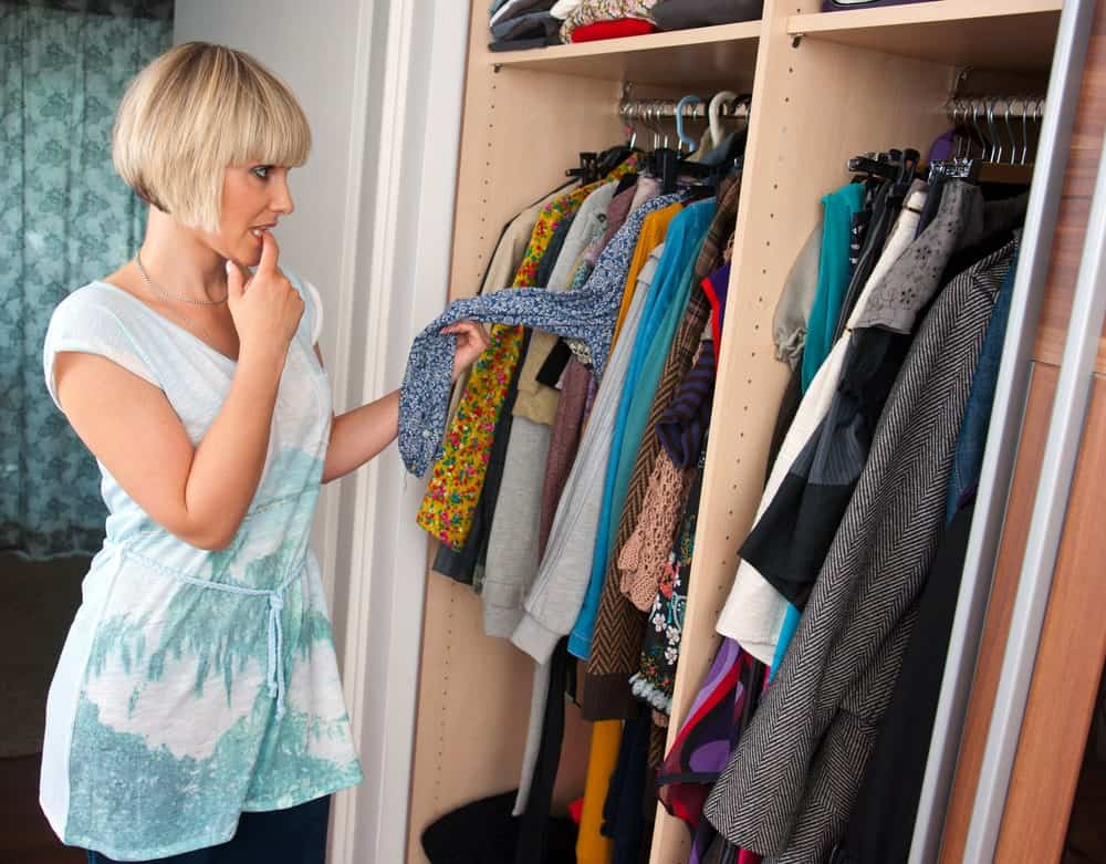 Woman choosing her clothes to wear from an open closet.