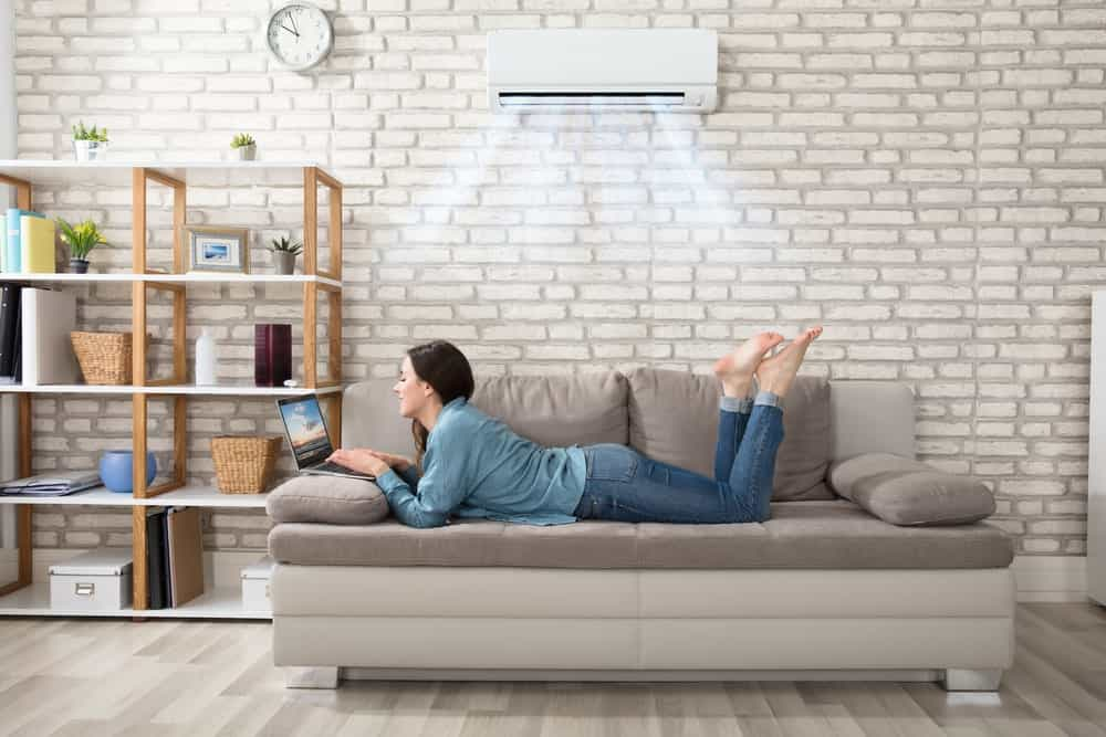 Woman lying on the living room sofa and working on her laptop while the air conditioning blasts above her.