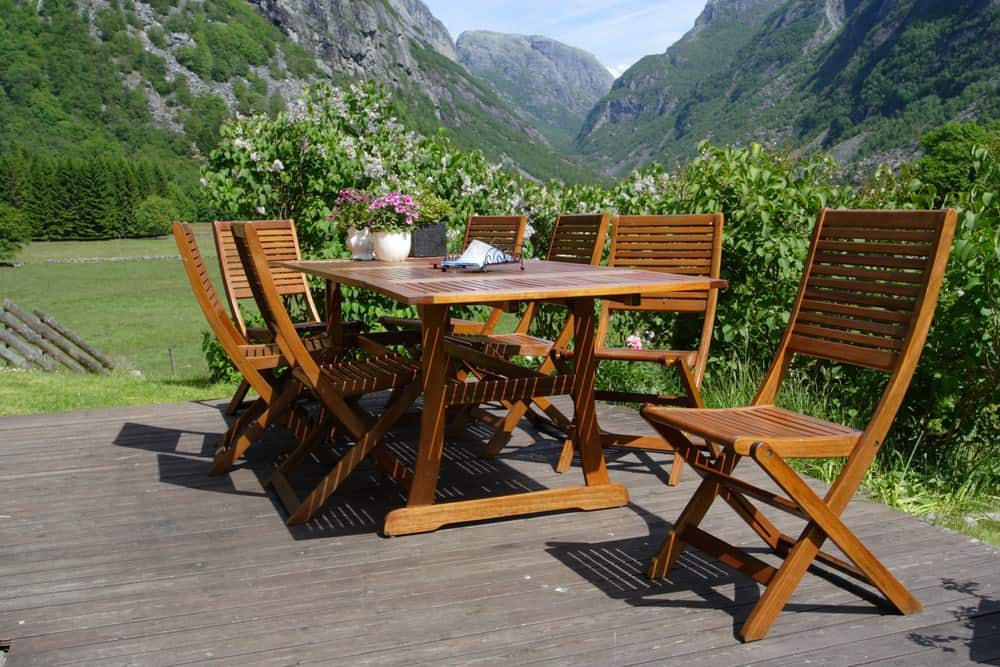 Wooden patio chairs and table on a stunning outdoor natural setting.