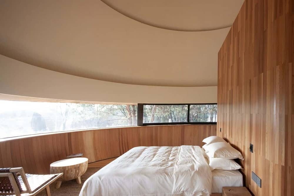 This is a view of the bedroom with a narrow set of glass windows running the middle of the curved wall across from the bed that is built into the wooden wall of the headboard.