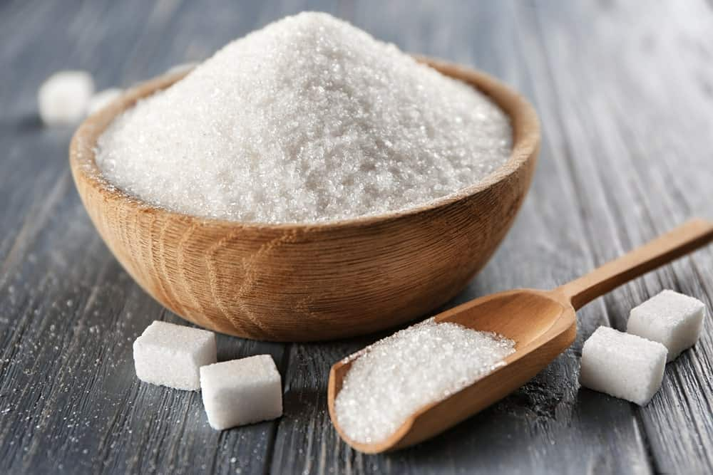 White Sugar in a bowl with a wooden spoon