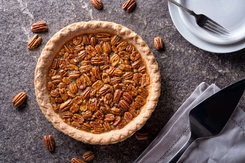 Top view of a pecan pie surrounded by nuts, a spatula on a table cloth, and a fork on an empty plate.