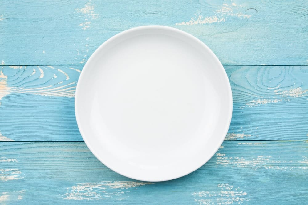 A white round plate on blue-painted wooden background.