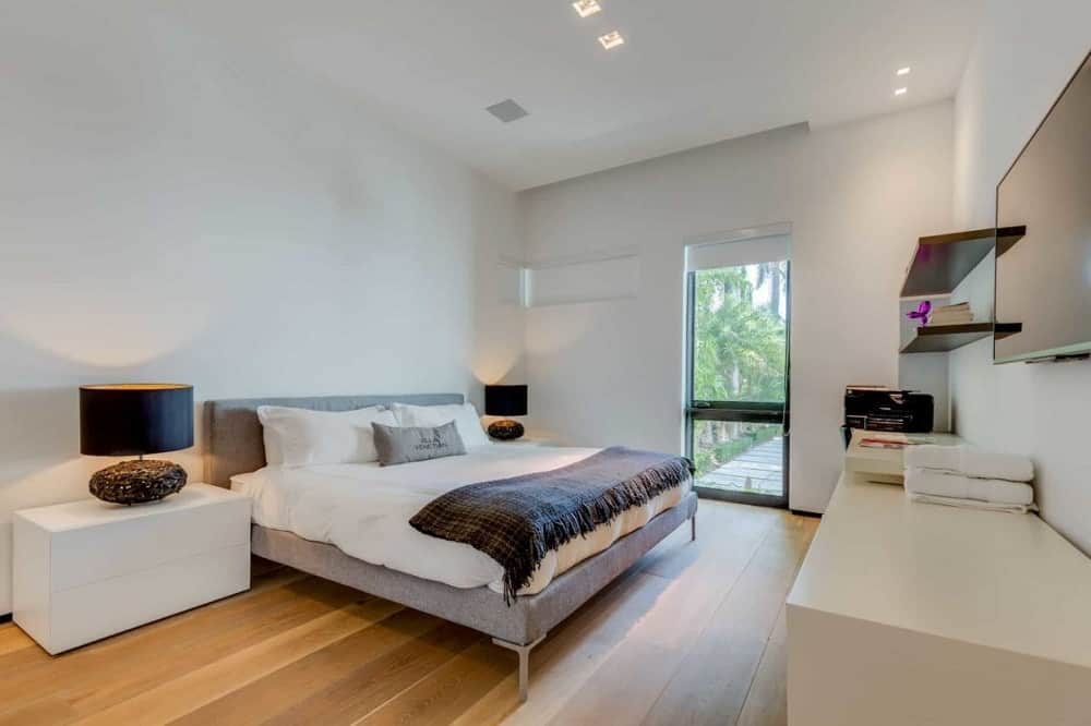 This is the bright and airy primary bedroom that has a gray bed flanked by white modern bedside drawers bearing black table lamps that stand out against the white walls.