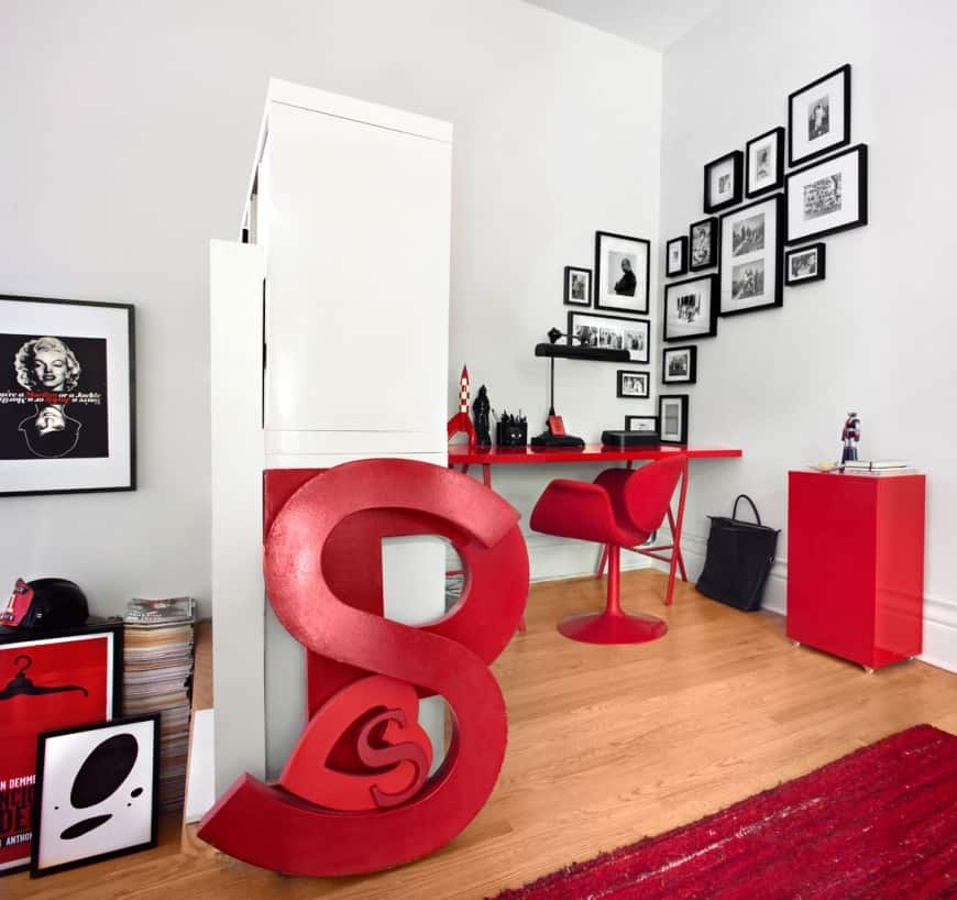 Tiny Eclectic home office with black-framed square and rectangle wall frames of varying sizes featuring black and white photos and white open space offset by the vivid red on the furniture pieces and accessories.