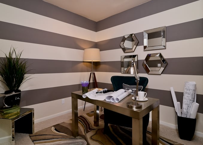 Gaudy small home office with gray and white walls, geometric chrome wall mirrors, floor lamp, and a chrome lamp and table standing on a rug with busy patterns.