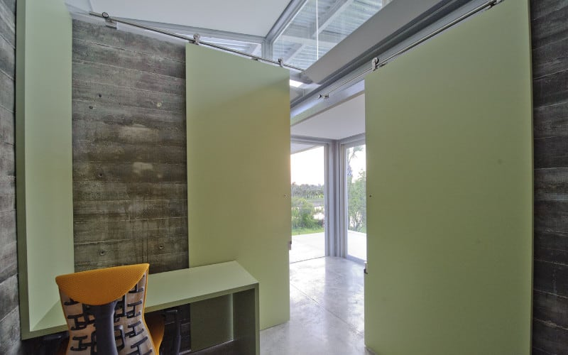 Small Industrial home office with gray rustic walls, green sliding doors, and a matching green L-shaped built-in desk.
