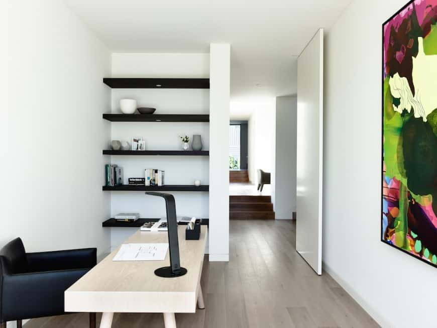 Small minimalist white home office with dark wooden shelves, stylish furniture in neutral colors, and a colorful painting for a pump of energy to the room.